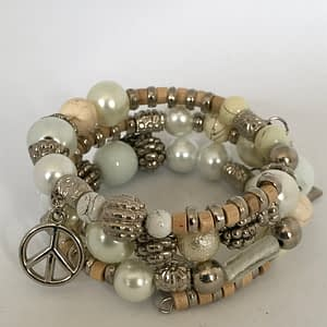 A striking Boho Bohemian Stack Bracelet with shiny, polished beads and small trinket charms adorn this bangle.